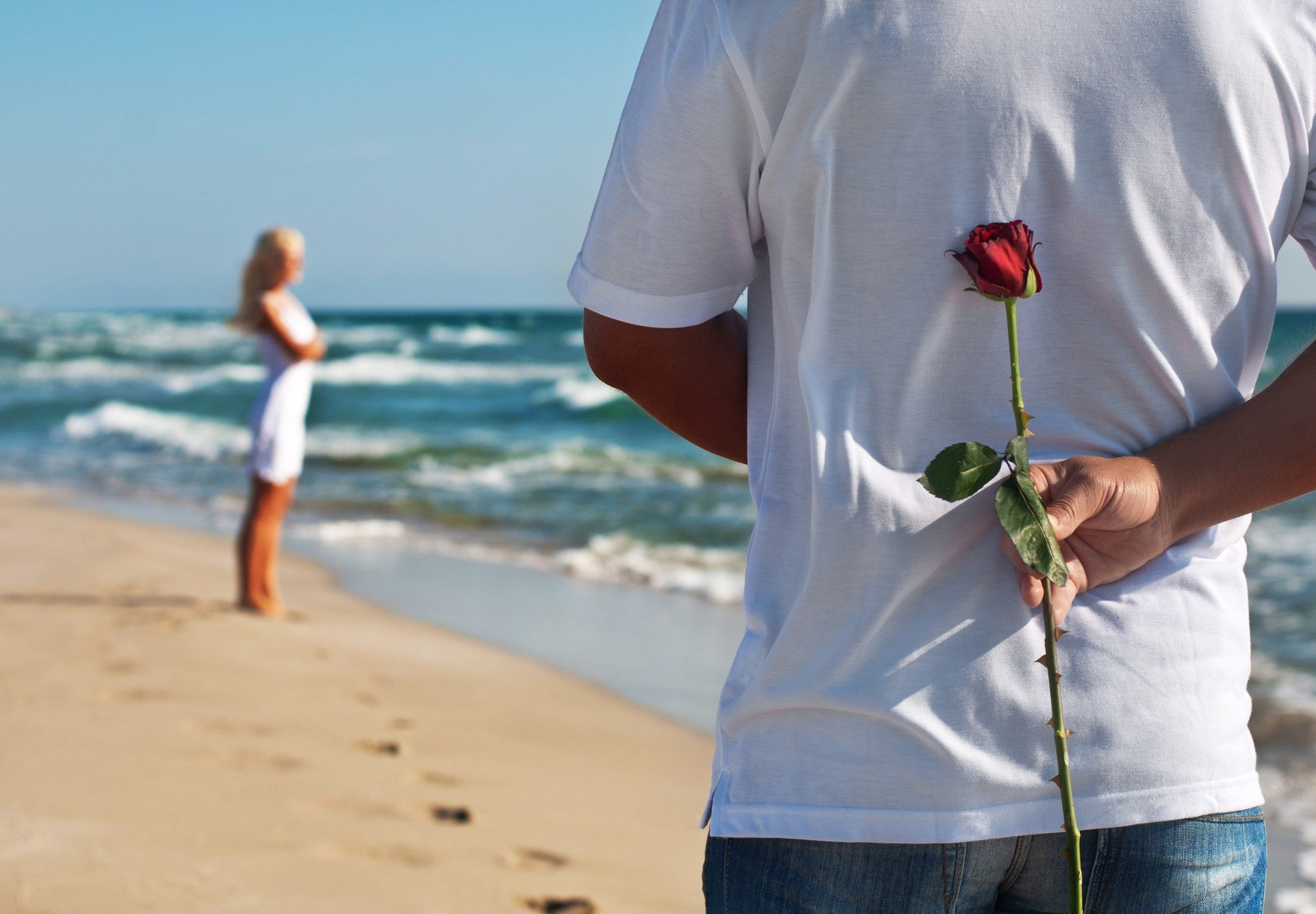 loving couple, man with rose waiting his woman on the sea beach